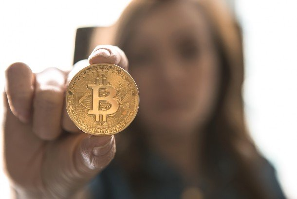 A woman holding a bitcoin coin in her hand